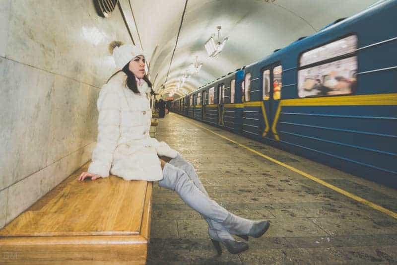Girl sitting on bench on platform of Vokzalna Metro Station in Kiev, Ukraine